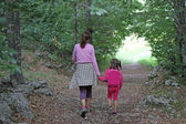 Mom and daughter holding hands walking in the middle of the fore — Stock Photo