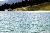 альпийская хижина на берегу красивого альпийского озера — Стоковое фото