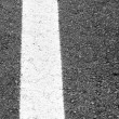 White line painted across the black asphalt road — Stock Photo