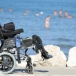 Stock Photo: Wheelchair for disabled people on Jetty of rocks by sea
