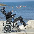 Wheelchair for disabled people on the Jetty of rocks by the sea — Stok fotoğraf