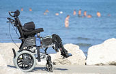 Silla de ruedas para las personas con discapacidad en el embarcadero de rocas junto al mar — Foto de Stock