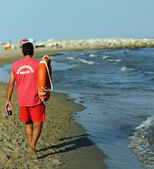 Lifeguard on the beach with a glass of soda and lifesaver — Stock Photo