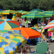 Umbrellas piled on the shores of the sea on the crowded beach — Stock Photo