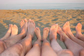 Barefoot of a family on the shore of the sea on the beach with c — Stock Photo