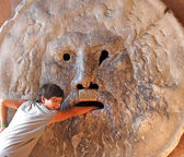 Teenager puts his hand inside hte mouth of truth in Rome Italy — Stock Photo