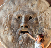 Girl puts her hand inside the mouth of truth in Rome — Stock fotografie