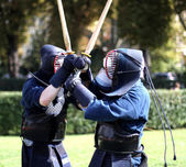 Two warriors of kendo fighting lottanon with bamboo swords — Stock Photo