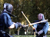 Two warriors of kendo fighting fight with bamboo swords in the — Stock Photo