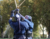 Fight between two warriors with mask and wooden stick — Stock Photo