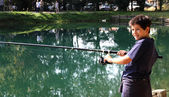 Guy with the fishing rod on the shores of Lake fishing — Stock Photo