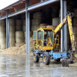 Stock Photo: Powerful Dozer pe collecting bales of hay in the stable