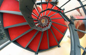 Spiral staircase with red carpet for a dizzying ascent — Stock Photo
