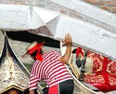 Gondolier passes under the bridge with its gondola — Stock Photo