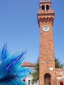 Klocktorn med klockan i ön murano och en glas-skulptur — Stockfoto