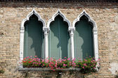 Luxurious flowery balcony in Venetian style with arched windows — Stock Photo