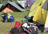Backpacks of hikers in the midst of camping tents — Stock Photo