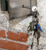 Varias llaves colgantes y una caja fuerte de acero — Foto de Stock