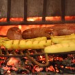 Stock Photo: Sausage cooked in fireplace with yellow polenta