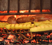 Sausage cooked in the fireplace with yellow polenta — Stock Photo
