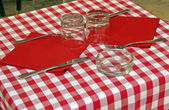 Set table with tablecloth red and white checked by an Italian re — Stock Photo