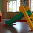Stock Photo: Plastic chute green and yellow in playroom inside asylum