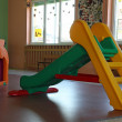 Plastic chute green and yellow in the playroom inside the asylum — Stock Photo