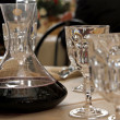 Carafe decanter with red wine in a table with many glass — Stock Photo