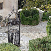 Ancient well in the cured Italian-style garden of a villa — Stock Photo
