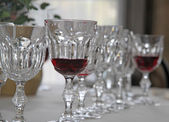 Elegant Bohemian crystal glasses lined up in set table for the p — Stock Photo