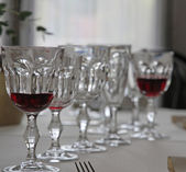 Elegant Bohemian crystal glasses lined up in set table — Stock Photo