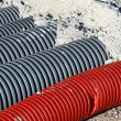 Red pvc corrugated hose and four gray pipes for laying electric — Stock Photo