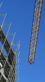 Cranes and scaffolding at a construction site with the backgroun — Stock Photo