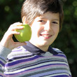 Teen holding a green ripe apple on a sunny day — Stock Photo