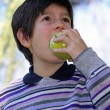 Stock Photo: Boy in striped wool sweater purple bite with hunger apple