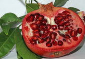 Pomegranate red ripe with beans very juicy and leaves — Stock Photo