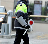 Policewoman with the paddle while directing traffic — Stock Photo