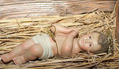 Baby Jesus is laid in the cradle in a manger — Stock Photo