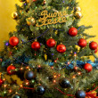 Stock Photo: Decorated Christmas tree with written happy holidays in Italian