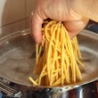 Cook's hand and thrown homemade spaghetti in boiling water — Stock Photo