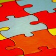 Puzzle with coloured puzzle of all colors as background — Stock Photo