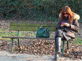 Woman on the bench while using your mobile phone — Stock Photo
