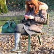 Womwaiting on bench while using your mobile phone — Stock Photo #38860265