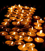 Wax candles lit by the faithful during the celebration of the Eu — Stock Photo