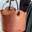 Copper pot carried by a peasant woman to the rural village — Stock Photo