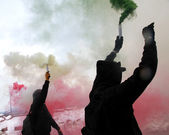 Protest with protesters dressed in black robes with green smoke — Stock Photo