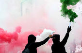Ultras fans with smoke red white and green dressed in black — Stock Photo