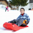 Cute boy falls from the fast descent with red bob — Stock Photo