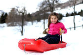 Pretty little girl playing in the snow with the bob toy — Stockfoto