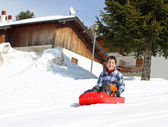 Young boy down the descent with red bob on white snow — Stock Photo